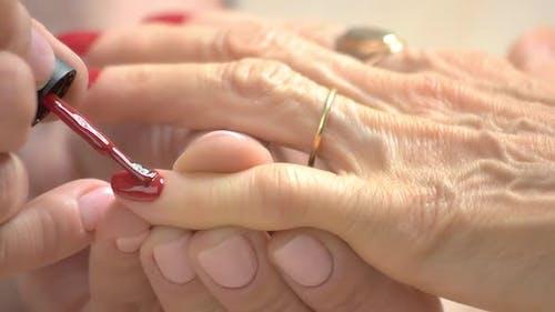 Manicurist Applying Red Varnish with Applicator.