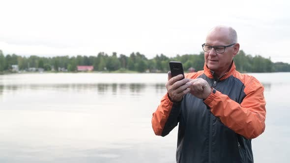 Cover Image for Happy Senior Man Using Phone By The Lake