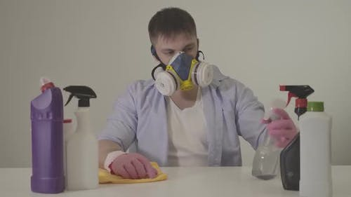 Portrait of Adult Caucasian Man in Respirator Spraying Cleansing Agent and Rubbing Table Indoors
