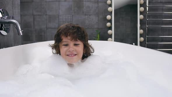 Thumbnail for Cheerful Little Boy with Brown Hair which Taking a Bath with Foam and Looking at Camera