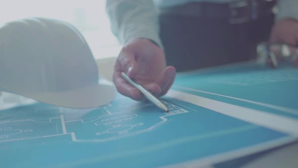Thumbnail for Young engineer-architect in a bright room works with blueprints laid out on a table