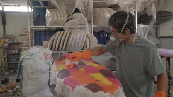 Craftsman Painting Surfboard with Different Colors