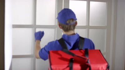 Courier in Face Mask and Gloves Delivering Pizza