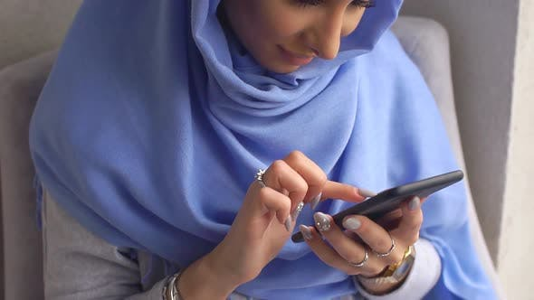 Thumbnail for Portrait of a Modern Muslim Woman. Young Woman in Hijab Dials Message on Mobile Phone