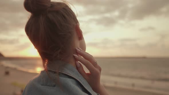 Young Woman Admiring the Sunset By the Sea
