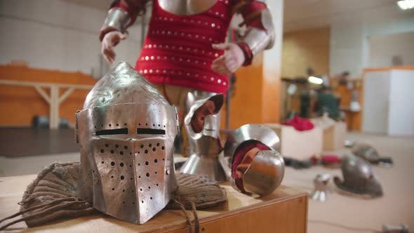 A Man in the Dressing Room Putting on the Armour Helmet