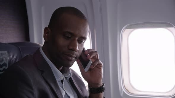 Thumbnail for Businessman talking on cell phone on airplane flight