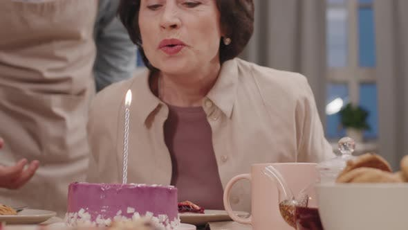Senior Woman Blowing Out Candle On Birthday Cake
