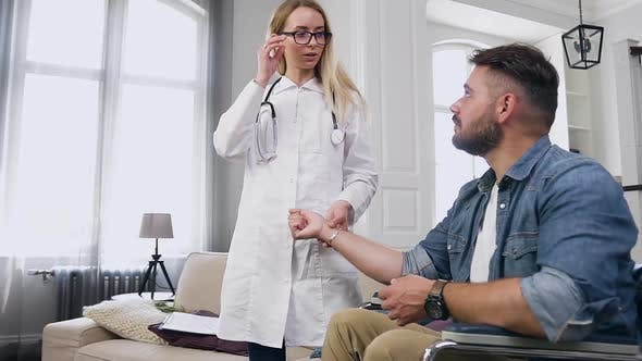 Professional Medical Assistant Checking Heart Rate to Balanced Young Bearded Man in Wheelchair