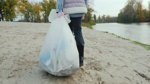 Thumbnail for A Volunteer Child Drags a Heavy Garbage Bag Along the Beach. Cleaning of Waste and Activism