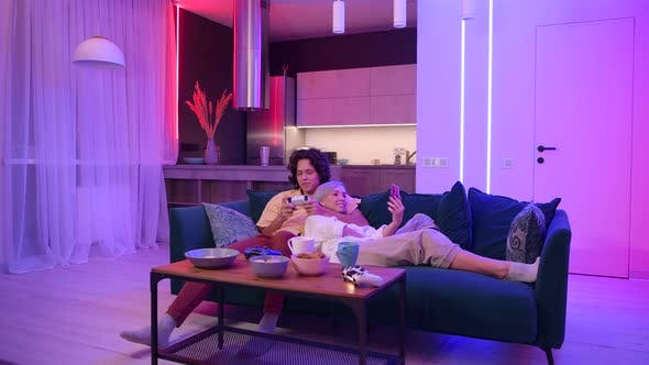 Thumbnail for Guy Playing Video Game While Girl Using Smartphone for Social Media. Spending Time Together at Home