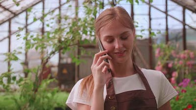 Young Girl Nursery Worker and Flower Greenhouse Speaks to a Client on the Phone