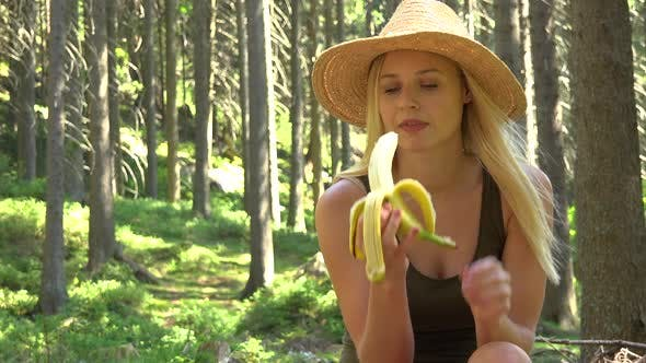 Thumbnail for A Young Beautiful Woman Sits in a Forest on a Sunny Day and Eats a Banana