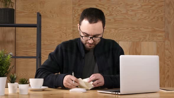 Thumbnail for Hipster Taking Notes Down From His New Laptop Computer While Browsing the Internet