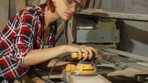 Diligent Female Carpenter Sanding Wood at the Workshop