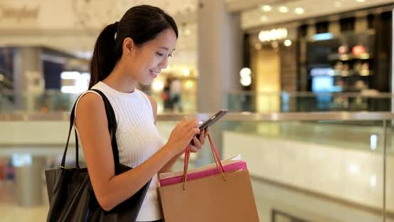 Cover Image for Woman using smart phone and holding paper bags in shopping mall