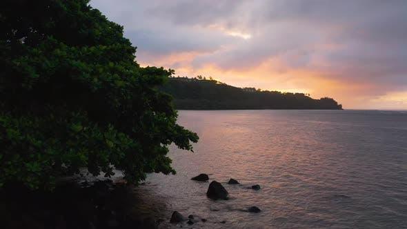 Thumbnail for Fly Away Drone Aerial Reveal Breathtaking Sunset Moody Sky Above Kauai Hawaii Beach Shore