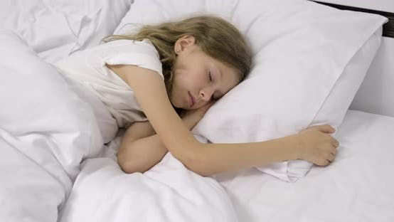 Thumbnail for Girl Child Ten Years Old with Long Curly Blond Hair Sleeping in White Bed on Pillow