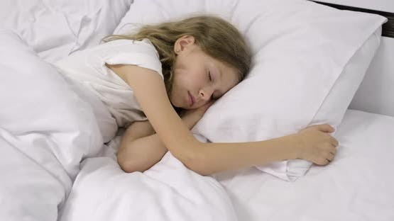 Girl Child Ten Years Old with Long Curly Blond Hair Sleeping in White Bed on Pillow