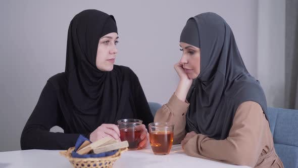 Thumbnail for Modest Muslim Woman in Hijab Calming Down Her Modern-looking Female Friend