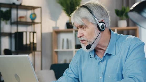 Old Man Using Laptop and Headset for Video Conversation