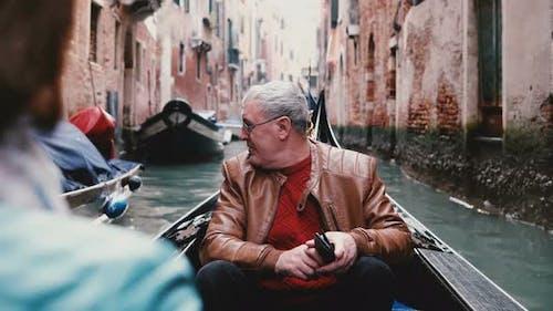 Glückliche Senior European Male Traveler in Gondel Aufgeregt, genießen Venedig Canal Tour Exkursion auf