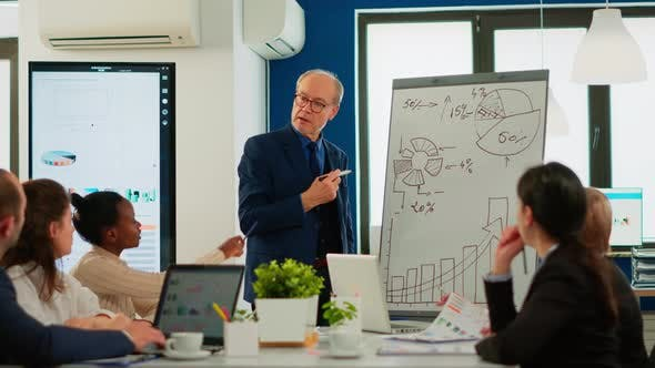 Senior Businessman in Eyeglasses and Formal Suit Drawing Financial Plan on Flipchart