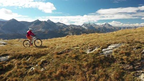 Aerial View Woman Mountain Biking on Ridge Side View