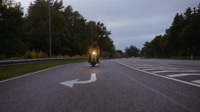 Motorcycle Taking a Turn on the Road With a Glimpse of the Sky at Dusk