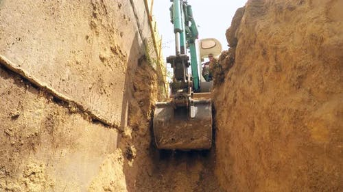 In the Trench, the Excavator Lifts the Earth