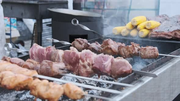 Shish Kebab on Skewers Is Cooked on Barbecue at a Street Food Festival