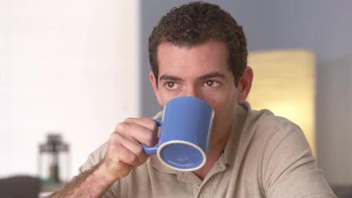 Man drinking coffee while looking away