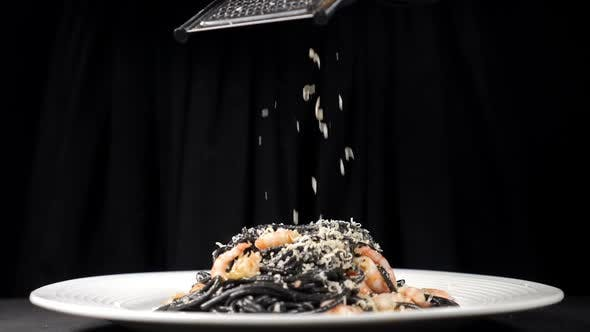 Chef Grating Hard Cheese on Freshlycooked Black Seafood Pasta