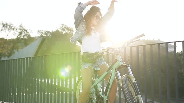 Cover Image for Girl in Stylish Clothing, Sunglasses with Long Hair Dancec in City while Standing with Bicycle