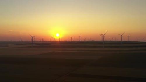 Eolian turbine farm at sunrise. Wind turbine silhouette. Wind field turbines