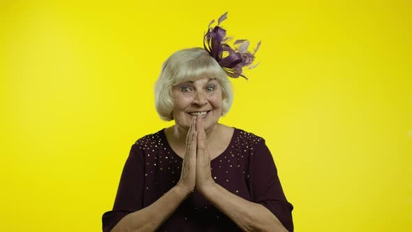 Positive Senior Old Blond Woman Appealing To Camera, Keeping Prayer Gesture and Asking Help