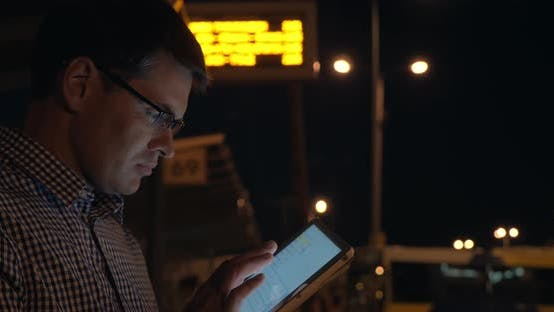 Thumbnail for Man with Tablet Computer on Bus Station at Night