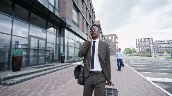 Thumbnail for Businessman Walking with Suitcases and Talking on Phone