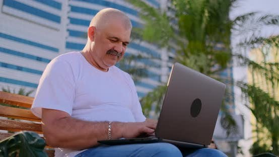 Thumbnail for Senior Man Sitting on a Park Bench Among the Palm Trees and Looking at Laptop Screen