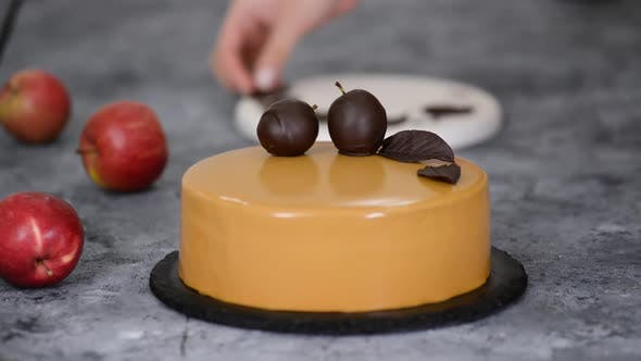 Thumbnail for Pastry Chef Decorating the Cake with Chocolate Apples and Leaves. Pastry Chef Decorated Modern