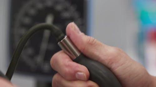 Tight shot of medical practitioner measuring blood pressure with gauge