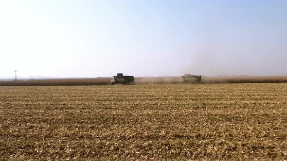 Two combine harvesters in cloud of dust during harvest