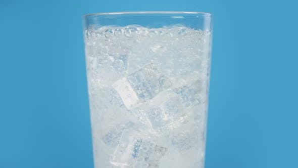 Thumbnail for Glass Full of Cold Sparkling Water with Ice Cubes on Blue Background Transparent Fizzy Drink