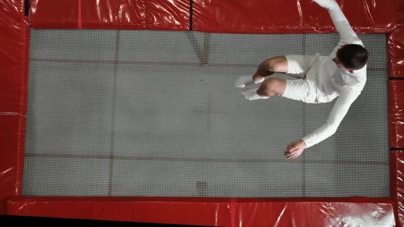 Thumbnail for Top View Gymnast Acrobat in White Clothes Performs a Somersault on a Trampoline in Slow Motion