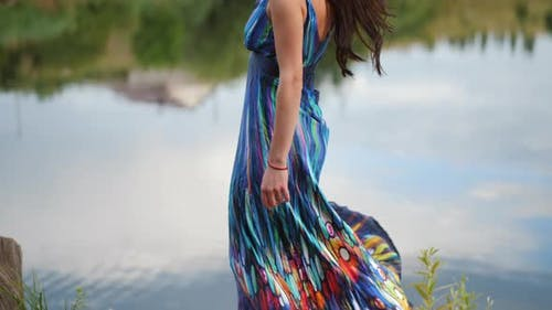 Beautiful Brunette Woman in a Dress Spinning on the Lake Shore