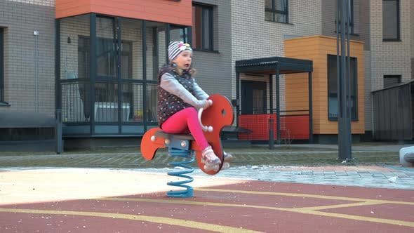 Cute Little Girl Enjoying Playing on a Playground