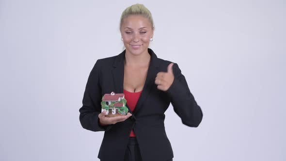 Cover Image for Young Happy Blonde Businesswoman Holding House Figurine and Giving Thumbs Up