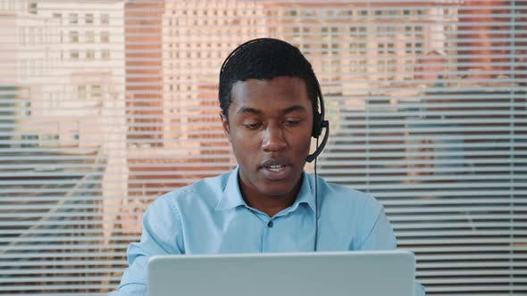 Thumbnail for Black Man in Headset Speaking with Somebody and Working on the Computer
