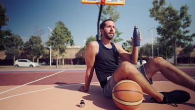 Tired Basketball Player After the Match Sits on the Basketball Field and Drinks Water