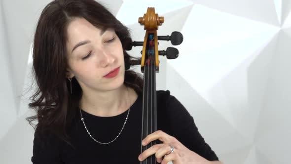 Thumbnail for zwei mädchen spielen die violinen eins auf dem cello in der weiß studio